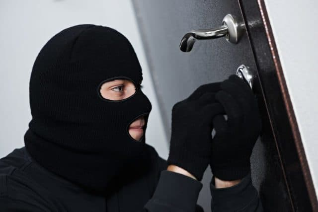Thief Burglar force lock metal door with a tool during house bre